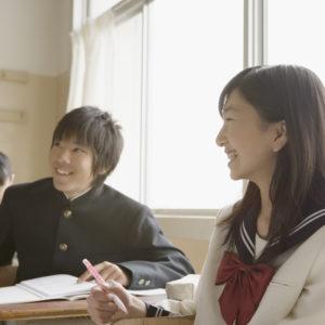 笑いながら楽しく学習している男女の学生
